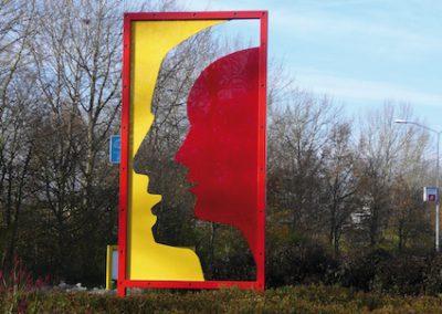 Theatraal - plexiglas gezichten op rotonde Almere Haven. Verwijzen naar Corrosia